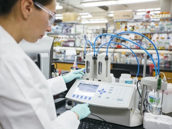 A person wearing laboratory safety equipment works with lab equipment.