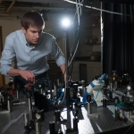 Erik Grumstrup, recipient of a U.S. Department of Energy early career award, makes adjustments to a laser used for testing solar cell materials in his laboratory at Montana State University in Bozeman. (MSU photo by Kelly Gorham).