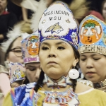 A Native American woman dressed in ceremonial regalia looks on to powwow dancers.