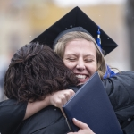 Mother and daughter hug in excitement after the fall 2019 commencement ceremony.