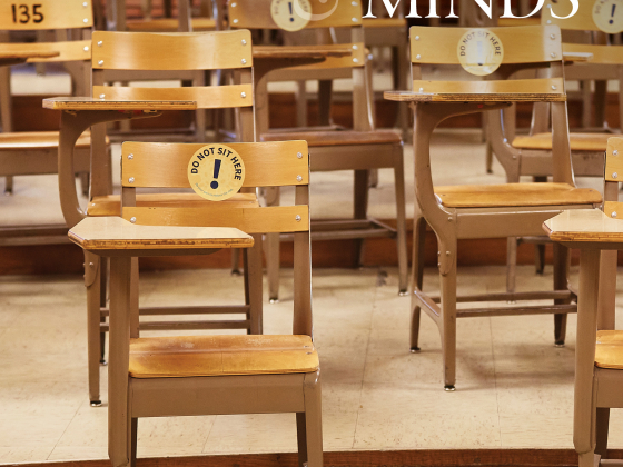 """Rows of old fashioned school desks on the steps of an auditorium with a round sticker labeled """"Don't sit here"""" on many of the desks including the one in the foreground.  """