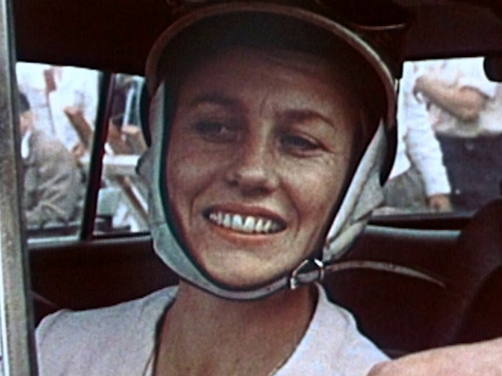 Photo of a smiling woman in a car and wearing a helmet. |