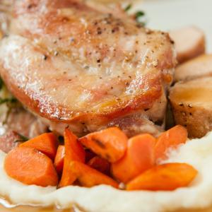 Sauteed pork chop and carrots over a bed of mashed potatoes.