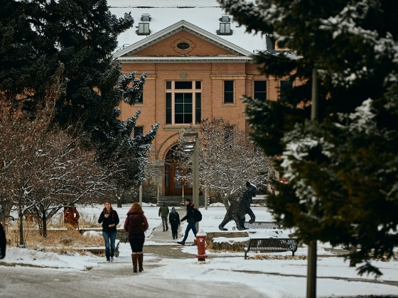 Students walk across a portion of the snowy Montana State University campus in front of a brick academic building. | Adrian Sanchez-Gonzalez/MSU