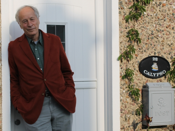 The author Richard Ford standing against a white door with the address Calypso over the adjacent mailbox. |
