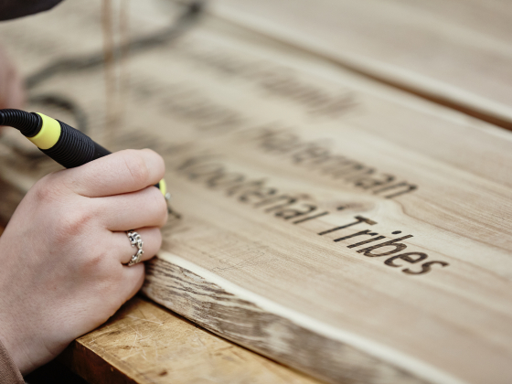 A detail view of text being written with a wood burning pen on a wood panel.   MSU Photo by Adrian Sanchez-Gonzalez