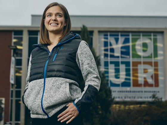 A woman poses for a photo outside a building with YOUR acronym | MSU Photo by Adrian Sanchez-Gonzalez