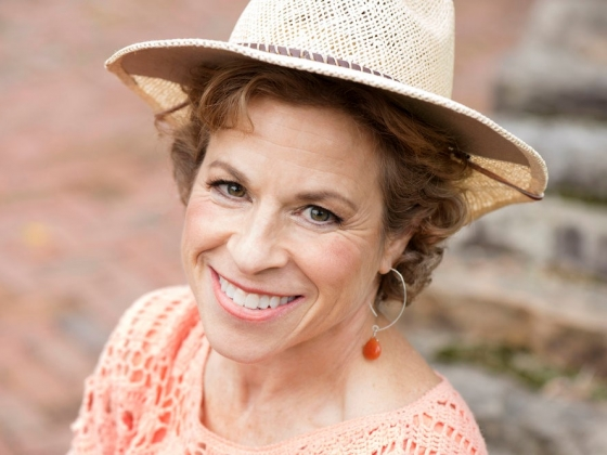 A portrait of Lori Rosolowsky wearing a brimmed straw hat.