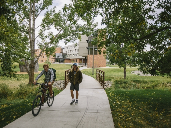 Student walking next to a cyclist on campus |