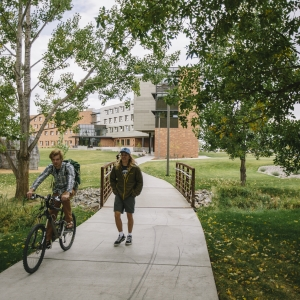 Student walking next to a cyclist on campus