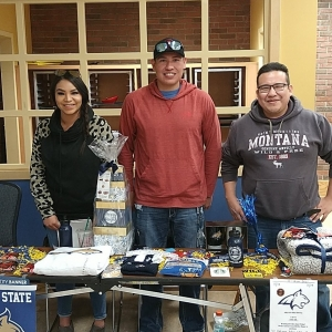 Three students stand in front of a table filled with MSU-branded items.