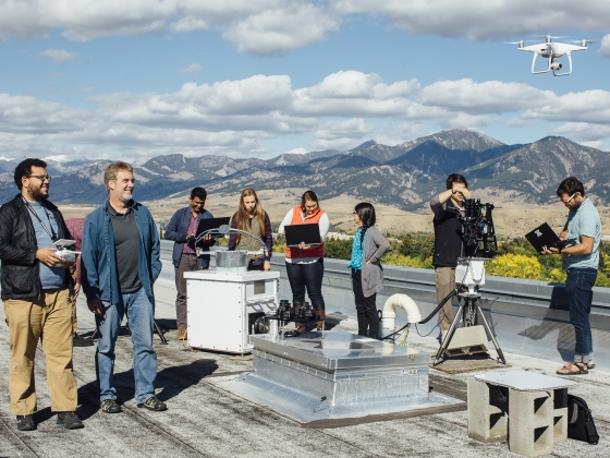 Students and faculty work with a variety of sky measuring equipment on a rooftop overseeing a mountain range. | MSU Photo by Adrian Sanchez-Gonzalez