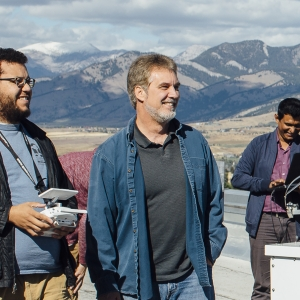 Students and faculty work with a variety of sky measuring equipment on a rooftop overseeing a mountain range.