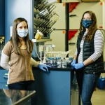 Two women in face masks inside a lab look toward the camera next to water samples.