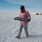 MSU researcher John Priscu takes a Niskin Bottle water sampler to a lab at an Antarctic field site for anaysis. Photo by JT Thomas.