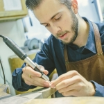 Jason Baide, a senior in studio arts at Montana State University, recently took first place in the Saul Bell International Jewelry Award for Emerging Artist. Baide has been working in his father's jewelry store, The Gem Gallery in downtown Bozeman, seen here on Monday, July 31, 2017, and learning from goldsmiths from a young age. MSU Photo by Adrian Sanchez-Gonzalez