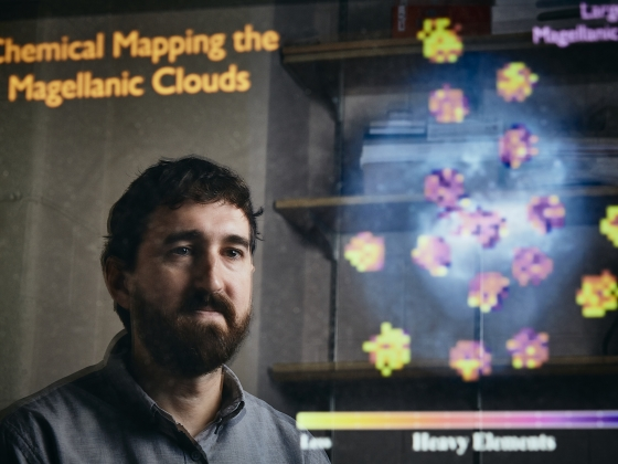 David Nidever poses for a portrait while reflected on a computer screen displaying star formations. | MSU Photo by Adrian Sanchez-Gonzalez