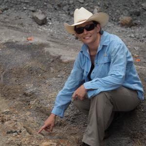Holly Woodward points at the Maiasaura fossil. |