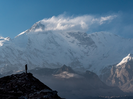Photo of a man standing on a hill with a large, snow-covered mountain in the background.  | Photo by Mary Hubbard