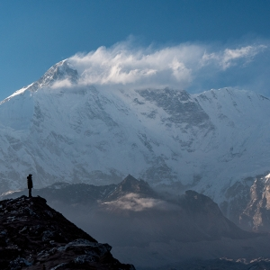 Photo of a man standing on a hill with a large, snow-covered mountain in the background.