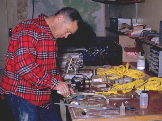 man wearing flannel shirt and jeans works at a workbench. |