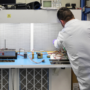 a small satellite on a work bench being worked on by man in white labcoat