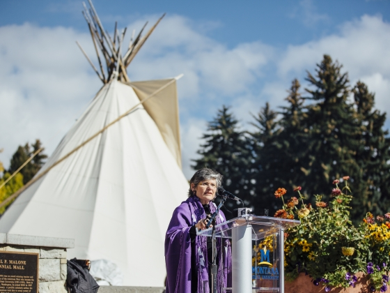 A medium view of President Cruzado speaking at podium with a teepee in background | MSU Photo by Adrian Sanchez-Gonzalez