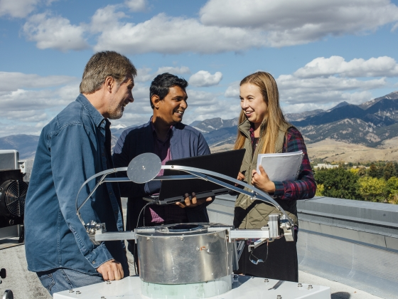 Three people, on a building roof with mountains in the background, standing next to photonics equipment.  |