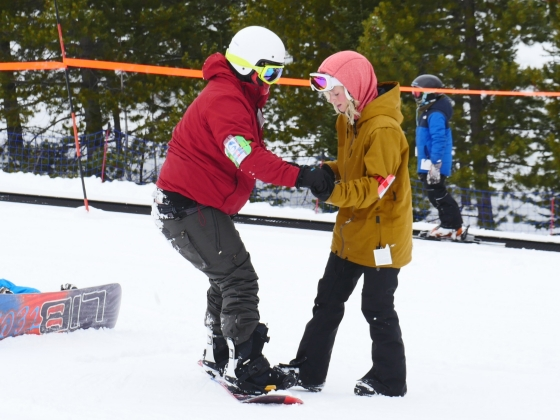 Photo of a person on a snowboard holding on to the hands of another person who is standing in the snow without a snowboard. |
