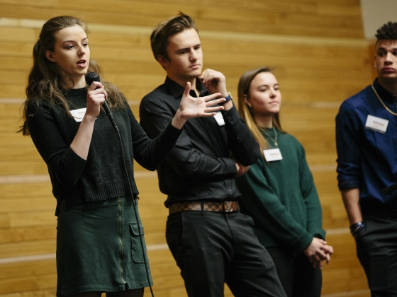 Business students speak through a microphone during a stage presentation | MSU Photo by Adrian Sanchez-Gonzalez