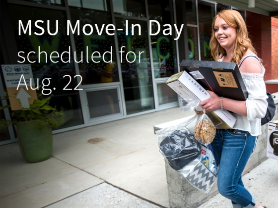 Students and family members carry belongings into the front door of a residence hall at Montana State. | Adrian Sanchez-Gonzalez/MSU