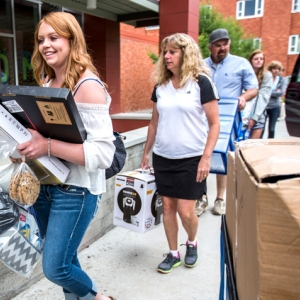 Students and family members carry belongings into the front door of a residence hall at Montana State.