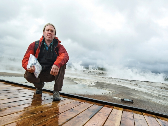 Photo of man in red jacket kneeling on boardwalk with geysers in background.   MSU photo by Kelly Gorham