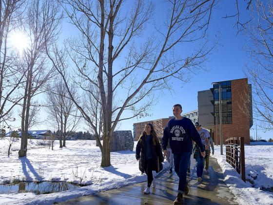 Photo of students walking down a path surrounded by snow with a bright blue sky and residence hall in the background. | MSU photo by Kelly Gorham