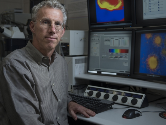 portrait photo of Phil Stewart with research computer screen behind him on desk |
