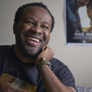 Portrait of a man smiling while looking out a window with a movie poster in the background.
