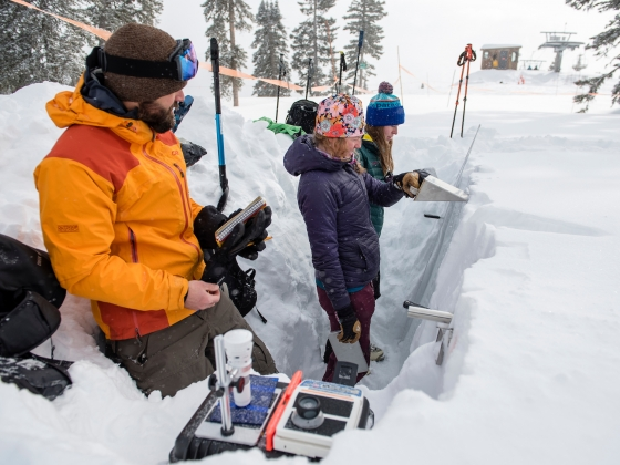 MSU researcher Kevin Hammonds and two helpers conducting a study in a snow pit at Bridger Bowl ski area  