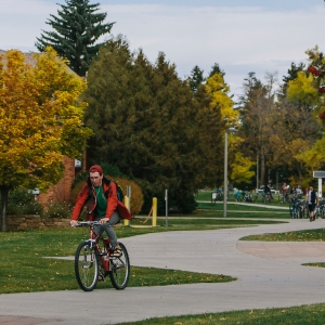 A bicyclist rides on the sidewalk beneath the noodle-shaped sculpture outside Barnard Hall at Montana State University during the fall season.