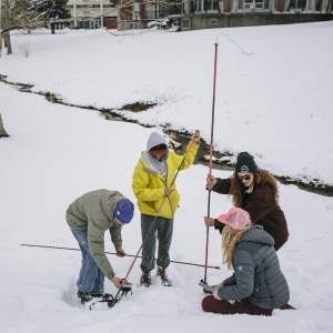 A group of students searching for a buried avalanche beacon.