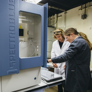 Lab technicians load water samples onto an optical emission spectrometer