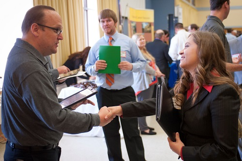 Student and organizational representative shaking hands at a career fair