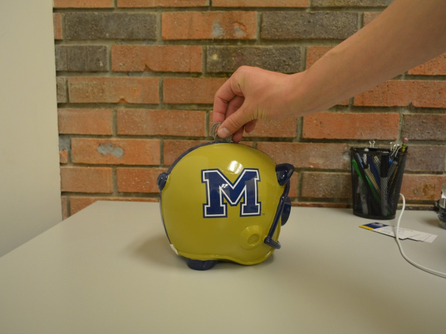Student dropping a coin into a piggy bank with MSU logo
