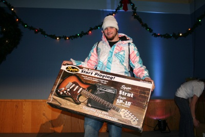 A skier poses with his new guitar (probably supposed to have come with that case)