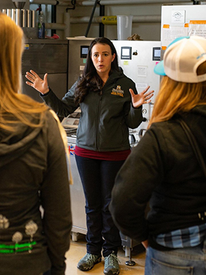 Hannah Turner leads attendees of the Pink Boots Winter Weekend even in a tour of the Malt Quality Lab