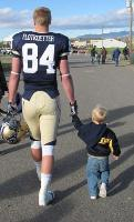 A little Bobcat heads back to the locker room with his hero. Photo submitted by Vicki Flotkoetter.