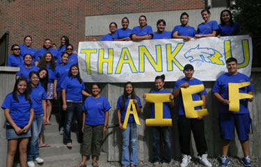 Students holding Thank You AIEF banner
