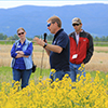 Perry Miller (second from right) gives a short presentation on winter canola at MSU's Post Farm near Bozeman. A group from the Montana Farmers Union visited the farm in June. (MSU photo by Tanya Reinhardt.)