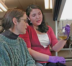 Kathi Trujillo and Tami Jo Old Coyote look over a vial of yeast in ...