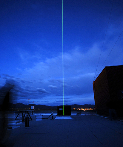 A green laser beam used for taking atmospheric measurements pierces the night sky above the Montana State University campus in Bozeman. MSU Photo by Kelly Gorham