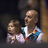 Shane Doyle holds his daughter, Lilian, as he waits to sing an honor song at Montana State University. (MSU photo by Kelly Gorham).